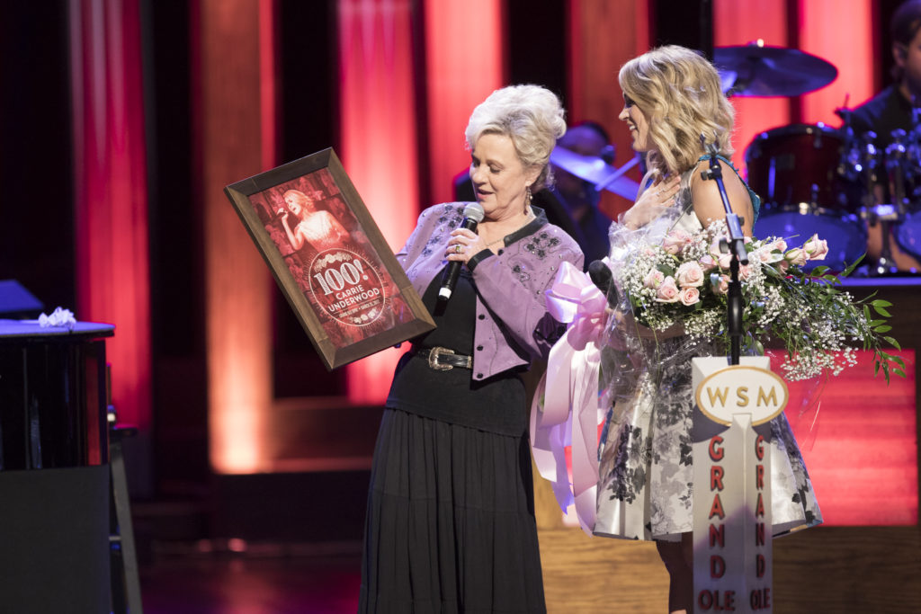 Connie Presenting Carrie with commemorative print and a rose bouquet
